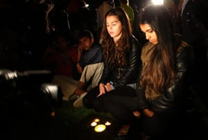 People sit behind burning candles for former president Nelson Mandela on hearing of his passing outside his Johannesburg home Thursday, Dec. 5, 2013.