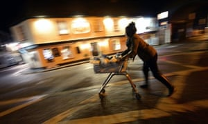 A woman hurries home with sandbags in a trolley, to protect her home in Sandwich, Kent.
