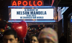Pedestrians pass beneath the Apollo Theatre in New York commemorating the life of South African leader Nelson Mandela.