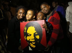 South Africans hold pictures of former South African president Nelson Mandela as they pay tribute in Johannesburg, South Africa.