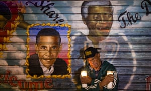 An artist who goes by the name 'Franco the Great' stands in front of a mural of South African leader Nelson Mandela that he painted in 1995, and later added U.S. President Barack Obama, on 125th Street in the Harlem neighborhood of New York.