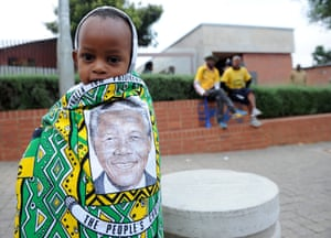 A child draped in a cloth with the image of Nelson Mandela on it, stands outside his former home, now museum, in Soweto, South Africa.
