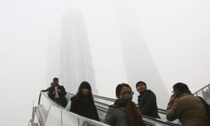 People use escalators with skyscrapers, covered with haze in the background, in Shanghai, China,