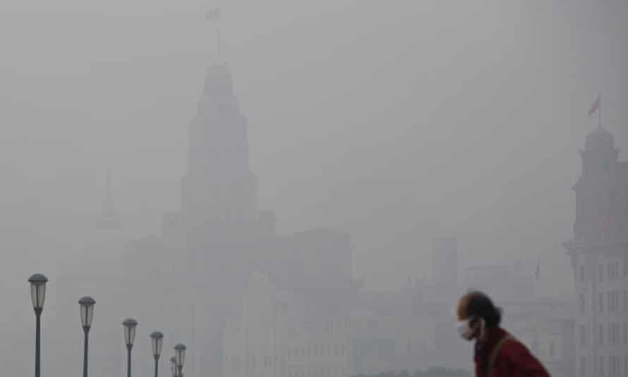 A man wears a face mask while walking on the Bund during a hazy day in downtown Shanghai.