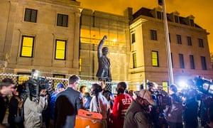 聚集在纳尔逊·曼德拉雕象附近的人们在华盛顿特区的南非使馆