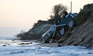 Collapsed houses lie on the beach after a storm surge in Hemsby.