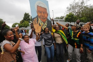 Mourners gather around a huge painting of Nelson Mandela outside the house of the late South African president Nelson Mandela in Johannesburg, South Africa.