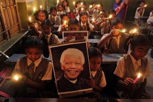 Indian schoolchildren hold candles and a portrait of Mandela as they pay tribute to him on hearing of his death, at a school in Ahmadabad.