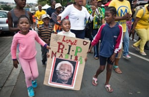 A young girl with a placard showing the face of Nelson Mandela, marches with others to celebrate his life, in the street outside his old house in Soweto, Johannesburg.
