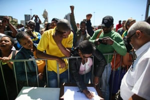 South African mourners sing and dance before signing a message book infront of the Cape Town City Hall where the late South African president Nelson Mandela made his first public address after being released from prison.