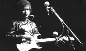 Bob Dylan playing an electric guitar on stage for the first time at Newport Folk Festival in 1965