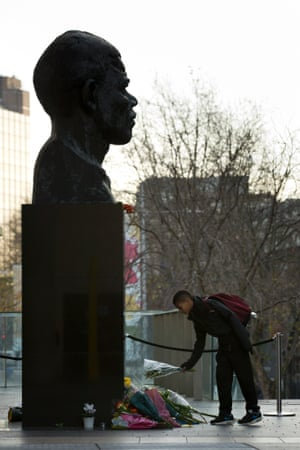 Pierre Jamme aged 12 from London lays a bunch of flowers by a statue of Mandela, at the side of the Royal Festival Hall in London.