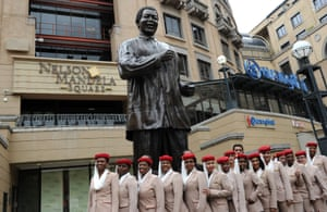 Cabin crew members pose in front of a statue of Mandela in Johannesburg.