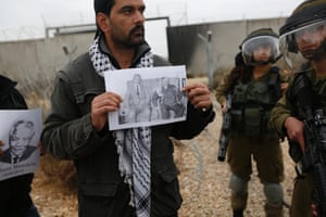 A Palestinian protester holds a placard depicting Mandela and former Palestinian leader Yasser Arafat, as he stands near Israeli soldiers at a weekly demonstration against Jewish settlements in the West Bank village of Bilin, near Ramallah.