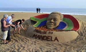 Tourists offer floral tributes near a sand sculpture of Mandela in Puri, India.