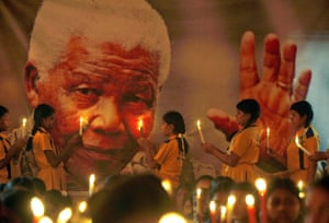 Schoolchildren hold candles near a giant portrait of Mandela in Chennai, India.