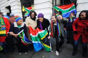 People sing songs outside the South African High Commission in London.