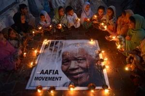 Pakistani schoolchildren hold lamps during a tribute  in Karachi.