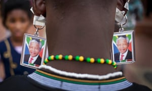 A man wears keyrings showing the face of Mandela taped to his ears to mimic earrings as he and others celebrate his life in Soweto.