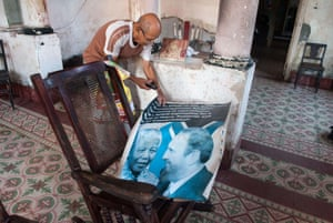 A man shows a poster of Cuban former president Fidel Castro and Mandela, at his home in Havana, Cuba.