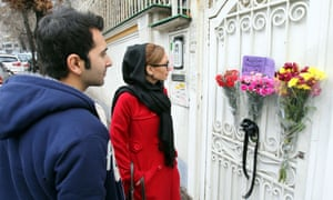 Iranians read a placard placed with flowers at the gate of the South African embassy in Tehran, Iran.