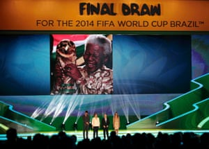 Brazilian President Dilma Rousseff (2nd L), FIFA President Sepp Blatter (2nd R), actor Rodrigo Hilbert and model Fernanda Lima stand on stage as a tribute to former South African President Nelson Mandela is shown on the screen during the draw for the 2014 World Cup at the Costa do Sauipe resort in Sao Joao da Mata, Bahia state, December 6, 2013. The 2014 World Cup finals will be held in Brazil from June 12 through July 13.