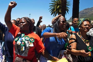 A woman with a Nelson Mandela t-shirt and badges sings and dances along with others in front of the Town Hall in Cape Town.