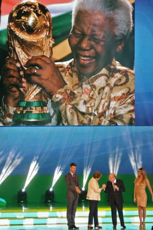 Brazilian President Dilma Rousseff  and FIFA President Joseph Blatter are flanked by presenters Rodrigo Hilbert and Fernanda Lima as a picture of former Mandela is displayed on a screen, during the final draw of the Brazil 2014 FIFA World Cup, in Costa do Sauipe, Brazil.