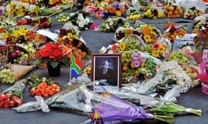 Flowers left by mourners surround a portrait of Mandela in the Sandton district of Johannesburg.