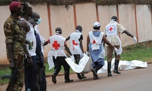 Rebels watch Red Cross workers retrieve bodies from the site of clashes in Central African Republic