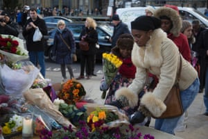 People lay flowers in Parliament Square by the statue of Nelson Mandela.