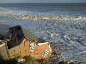 A house, rented by Robin Adams, fell into the sea in Hemsby, Norfolk, after the combined storm and tidal surge swept away the underside of the cliff it was perched on.