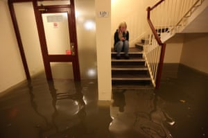 A resident sits on the stairs of a block of flats in Boston, where water has flooded the entrance area.