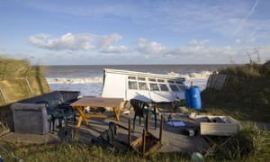 The furniture from a chalet home is left on the cliff after the building fell into the sea on the Norfolk coast.