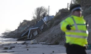 Members of the emergency services assess the damage after a night of a severe storm along Britain's North Sea Coast.