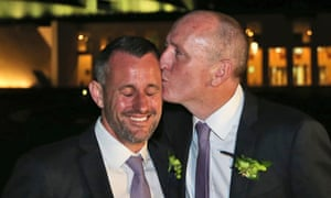 Stephen Dawson, right, kisses his husband Dennis Liddelow after their historic marriage.