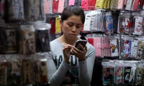 Chinese vendor uses mobile phone in mobile case stall