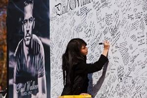 Paul Walker memorial: A fan signs a memorial board