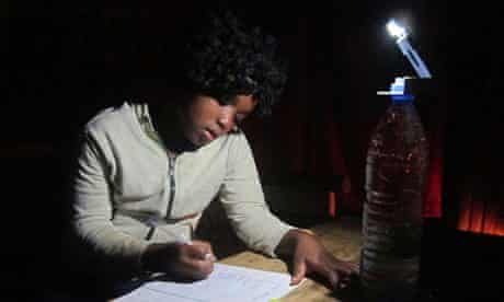 A woman works by the light of a WakaWaka lamp