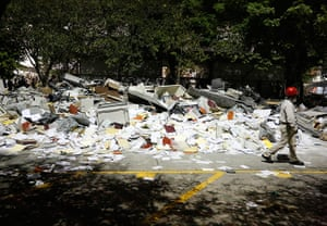 Mexico explosion: A worker walks past debris piled outside