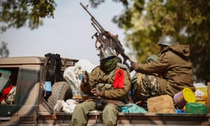 Malian troops patrol the northern town of Diabaly in Mali. Amnesty International claims Malian soldiers have executed dozens of civilians after French-led forces drove rebels from the area. Luke Harding reports.