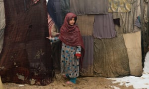 An internally displaced Afghan girl waits to receive donations at Nassaji Camp, east of Kabul. Afghanistan's internally displaced population has reached half a million according to the UN refugee agency, though the actual number is likely to be much higher.