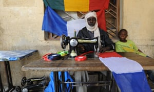 A tailor sews a French flag in Gao, Mali. France's president Francois Hollande is preparing to visit Mali as French-led troops worked today to secure the last Islamist stronghold in the north after a rapid offensive against the extremists.