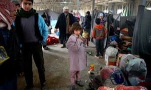 A girl tries on a donated jacket as Syrians arrive at Za'atari refugee camp in Mafrq, Jordan