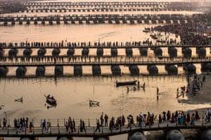 Maha Kumbh : Hindu pilgrims make their way over pontoon bridges near Sangam