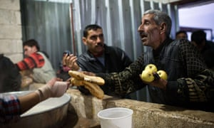 An internally displaced Syrian refugee collects  apples and some bread at a refugee camp at Azaz along the Syrian-Turkish border.