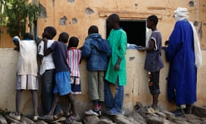 Malian children look at the heavily shelled police station in Gao, northern Mali this morning, one day after Mujao fighters engaged in a firefight with Malian forces.