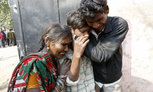 The mother of a stampede victim mourns with her two sons outside the mortuary in Allahabad, Uttar Pradesh, India. At least 36 Hindu pilgrims died in a stampede at a railway station near the Kumbh Mela religious festival in central India at the weekend.