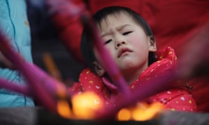 A child tries to light joss sticks at a temple in Shanghai, China, this morning, on the second day of Chinese new year