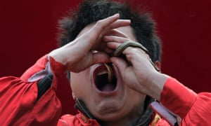 More hi-jinks from China as a performer inserts a live snake through his nose and mouth during a performance at the Ditan Temple fair celebrating the New Year in Beijing.